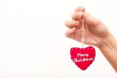 Main avec un coeur avec le Joyeux Noël de message Images stock