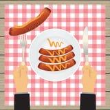 Main avec un couteau et des saucisses d'un plat illustration stock