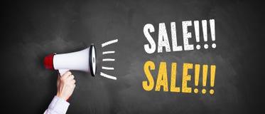 Main avec un mégaphone devant un tableau noir avec la vente de ` de message ! ! ! Vente ! ! ! ` images libres de droits