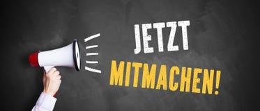 Main avec un mégaphone devant un tableau noir avec le ` allemand de s'inscrire de ` de message photographie stock libre de droits