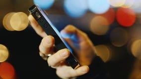 Main avec un téléphone portable sur un fond des lumières brouillées clips vidéos