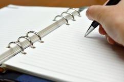 Main avec une écriture de crayon lecteur sur le livre blanc Image libre de droits