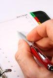 Main avec une écriture rouge de crayon lecteur dans un organisateur Photos libres de droits