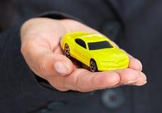 Main avec une voiture jaune Image stock