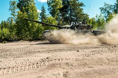 Main battle tank are going to dust on a forest road Royalty Free Stock Photos