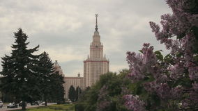 Main building of Moscow State University. Also known as MGU behind lilac bushes on a cloudy day stock footage