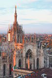 Main cathedral and italian flag at sunset in Milan Royalty Free Stock Photos
