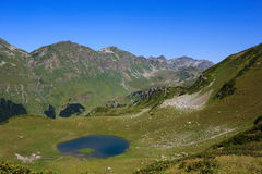 Main Caucasian Ridge and mountain lake surrounded with alpine meadows Stock Image
