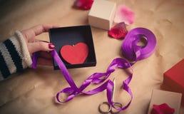 Main caucasienne blanche enveloppant le jouet en forme de coeur dans la boîte sur gagné Image libre de droits