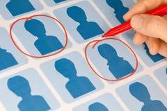 Main choisissant des candidats avec le crayon lecteur rouge Photos stock