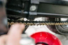 Main cleans motorbike chain. With spray cleaner Royalty Free Stock Photo