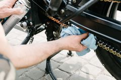 Main cleans motorbike chain Royalty Free Stock Photos