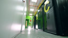 Main corridor of the server room with green walls. Servers in data center. Main corridor of the server room with green walls. 4K stock video footage