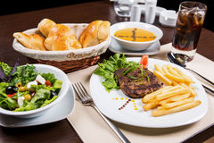Main course, soupe, salad, bread and drink for dinner. Pumpkin soupe, green salad, beef steak with potato. restaurant menu Stock Images