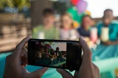 Main cultivée de personne photographiant des enfants par le téléphone portable Image libre de droits