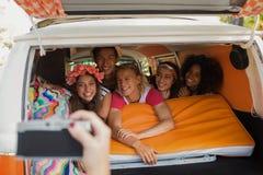 Main cultivée photographiant les amis de sourire dans le camping-car Photo libre de droits