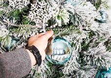 Main décorant un arbre de Noël Photo libre de droits