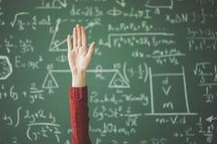 Main d'étudiant derrière le panneau de craie vert Photo libre de droits