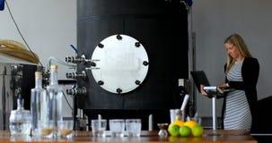 Main-d'œuvre féminine à l'aide de l'ordinateur portable dans l'usine 4k de distillerie banque de vidéos