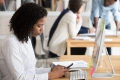 Main-d'œuvre féminine d'afro-américain à l'aide du téléphone sur le lieu de travail partagé image stock