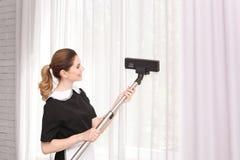 Main-d'œuvre féminine enlevant la poussière des rideaux avec l'aspirateur professionnel, à l'intérieur images stock