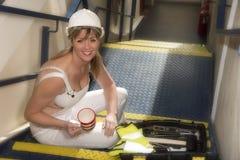 Main-d'œuvre féminine prenant une pause café se reposant avec une boîte à outils photographie stock libre de droits