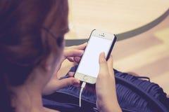 Main d'adolescente tenant le téléphone intelligent avec l'écran vide Photographie stock