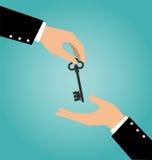 Main d'affaires donnant une clé de maison à une autre main Photos stock