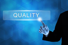 Main d'affaires poussant le bouton de qualité Image stock