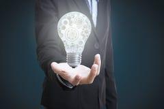 Main d'affaires tenant l'ampoule électrique avec des roues de vitesse Images stock
