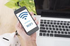 Main d'affaires tenant le téléphone intelligent avec l'accès gratuit de wifi photo libre de droits