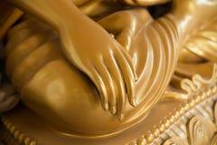 Main d'or de Bouddha sur le genou de la statue photos stock