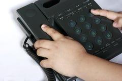 Main d'enfant à un téléphone Photo libre de droits