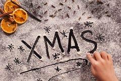Main d'enfant écrivant Noël en farine Photo libre de droits