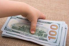 Main d'enfant en bas âge jugeant le paquet de billet de banque du dollar US disponible Photographie stock