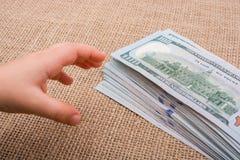 Main d'enfant en bas âge jugeant le paquet de billet de banque du dollar US disponible Photos stock