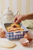 Main d'enfant garnissant la pâte lisse de gâteau mousseline avec la tranche de nectarine Photographie stock libre de droits