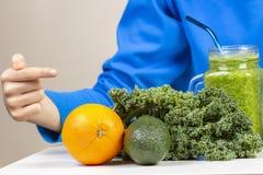 Main d'enfant indiquant le pot de smoothie et les légumes et le fruit sains sur la table photos stock