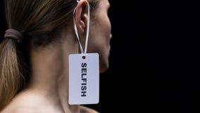 Main d'homme accrochant le label égoïste sur l'oreille femelle, montrant le manque de respect et mortifiant banque de vidéos