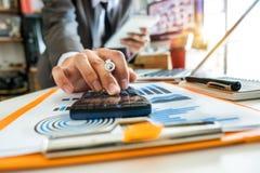 Main d'homme d'affaires fonctionnant avec des finances au sujet de coût et calculatrice et ordinateur portable photo libre de droits