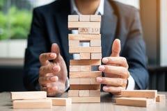 Main d'homme d'affaires plaçant ou tirant le bloc en bois sur la tour Planification des affaires, gestion des risques photographie stock