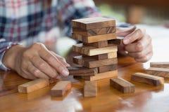 Main d'homme d'affaires retirant ou plaçant le bloc en bois sur le remorquage image libre de droits