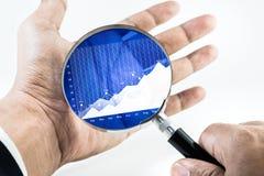 main d'homme d'affaires tenant l'agrandissement avec le diagramme croissant de graphique Images libres de droits