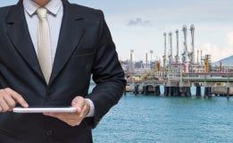 Main d'homme d'affaires tenant le comprimé avec le backgrou de canalisation de pétrole Photographie stock libre de droits