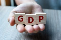 Main d'homme d'affaires tenant le cube en bois avec le produit intérieur brut des textes de PIB sur le fond de table Financier, g photos stock