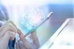 Main d'homme d'affaires tenant le téléphone intelligent se reliant à l'Internet et aux icônes sociales de media Photos stock