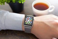 Main d'homme avec la montre d'Apple et icône d'APP sur l'écran Photographie stock