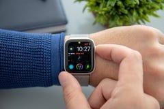 Main d'homme avec la série 4 de montre d'Apple au-dessus de la table photo stock