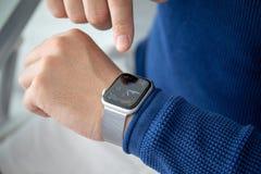 Main d'homme avec la série 4 de montre d'Apple dans la maison photographie stock