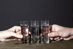 Main d'homme avec le verre de vodka Photographie stock libre de droits
